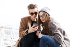 Couples utilisant le téléphone portable ensemble sur la plage en automne Image libre de droits