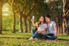 Couples utilisant le téléphone portable prenant un selfie en parc Photographie stock libre de droits