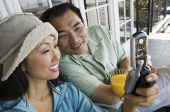 Couples utilisant le téléphone portable sur le porche Photo libre de droits