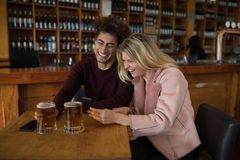 Couples utilisant le téléphone portable tout en ayant le verre de bière dans la barre Images libres de droits