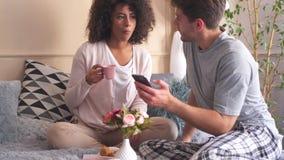 Couples utilisant le téléphone portable tout en prenant le petit déjeuner dans le lit banque de vidéos