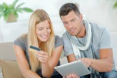 Couples utilisant leur comprimé à faire des emplettes en ligne Photographie stock libre de droits
