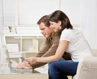 Couples utilisant par la carte de crédit à faire des emplettes en ligne Photos libres de droits