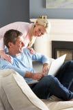 Couples utilisant se reposer de détente d'ordinateur portatif sur le sofa Photographie stock