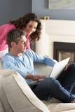 Couples utilisant se reposer de détente d'ordinateur portatif sur le sofa Photos stock
