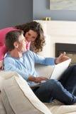 Couples utilisant se reposer de détente d'ordinateur portatif sur le sofa Image libre de droits