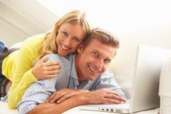Couples utilisant se reposer de détente d'ordinateur portatif sur le sofa Photo libre de droits