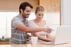 Couples utilisant un carnet tout en ayant le café Images stock
