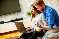 Couples utilisant un carnet tout en se reposant sur le plancher Image libre de droits