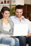 Couples utilisant un ordinateur portatif à la maison Photos libres de droits
