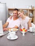 Couples utilisant un ordinateur portatif tout en prenant le petit déjeuner Photo stock