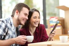 Couples utilisant un téléphone tout en déplaçant la maison Photographie stock libre de droits