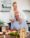Couples végétariens heureux souriant et faisant cuire des légumes Photographie stock libre de droits