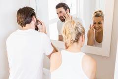 Couples vérifiant leur peau dans la salle de bains Photos libres de droits