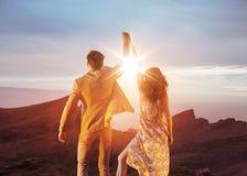 Couples victorieux regardant le beau coucher du soleil Photographie stock libre de droits