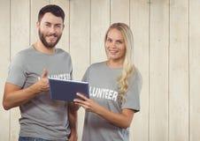 Couples volontaires utilisant les pouces numériques de comprimé et de représentation  Image stock