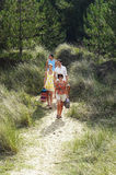 Couples Walking On Beach Trail Stock Photo