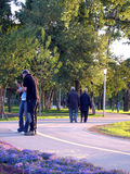 Couples walking in park. Rear view of senior couple walking on road through park with young couple in foreground royalty free stock image