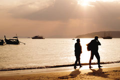 Couples walking to the sunset Royalty Free Stock Photos