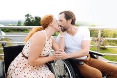 Couples wheelchaired gentils embrassant dehors Photo libre de droits