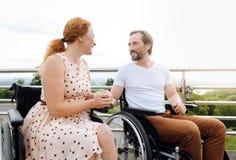 Couples wheelchaired par aîné positif appréciant la promenade Images libres de droits