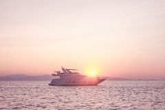 Couples on yacht at sunset. Two couples enjoying pink romantic sunset on private modern luxury yacht anchored at Mediterranean sea - luxury holidays and travel Royalty Free Stock Photos