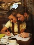 Couplestudents felices jovenes en café, visión a través de una ventana Fotografía de archivo libre de regalías