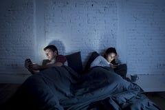 Couplez à la maison dans le lit tard la nuit utilisant le téléphone portable dans le problème de transmission de relations Photos stock