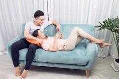 Couplez à la maison la détente sur le sofa avec le comprimé numérique Images stock