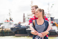 Couplez étreindre au pilier de port regardant des bateaux Images stock