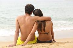 Couplez étreindre en regardant l'océan sur la plage image stock