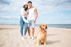 Couplez étreindre et marcher avec le chien sur la plage Photographie stock