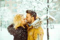 Couplez étreindre et regarder dans les yeux de chacun dans la neige Image libre de droits
