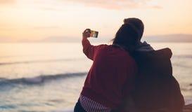 Couplez étreindre sur le lever de soleil d'océan de plage de fond, prenez les photos sur le smartphone mobile, deux personnes rom Photo stock