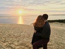 Couplez étreindre tout en observant la vue de coucher du soleil de la dune de Pyla, plus haute en plage sablonneuse de l'Europe F photo stock
