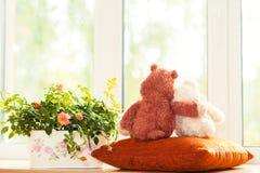 Couplez aimer en embrassant des jouets d'ours de nounours se reposant sur le fenêtre-filon-couche Photos stock