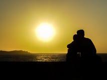 Couplez apprécier le coucher du soleil aux moulins à vent dans Mykonos Photos libres de droits
