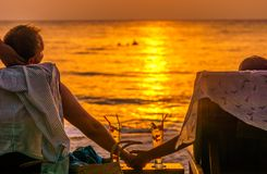Couplez apprécier le coucher du soleil avec Coctails sur la plage de Koh Kood en Thaïlande Image libre de droits