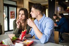 Couplez apprécier le déjeuner mangeant des aliments de préparation rapide se reposant au café image libre de droits