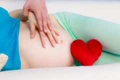 Couplez attendre le bébé, leur ventre enceinte émouvant de mains Photo stock