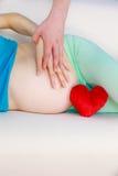 Couplez attendre le bébé, leur ventre enceinte émouvant de mains Photographie stock libre de droits