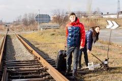 Couplez attendre le train près d'un passage à niveau Image stock