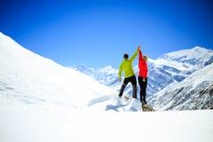 Couplez augmenter le succès d'homme et de femme en montagnes d'hiver Image stock