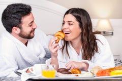 Couplez avoir l'amusement au petit déjeuner dans la chambre d'hôtel Photographie stock