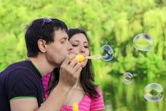 Couplez avoir l'amusement avec des bulles de savon dans le parc photographie stock libre de droits