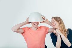 Couplez avoir l'amusement avec des tasses de café sur la tête masculine Photo libre de droits