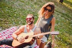 Couplez avoir l'amusement avec la guitare sur un pique-nique Photos stock
