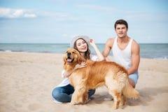 Couplez avoir l'amusement avec le chien sur la plage Photo libre de droits