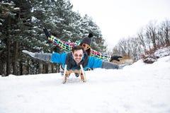 Couplez avoir l'amusement le jour d'hiver de neige en belle montagne Images libres de droits