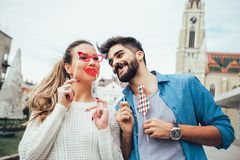 Couplez avoir l'amusement tenant la moustache et le bâton de lèvres artificiels image libre de droits